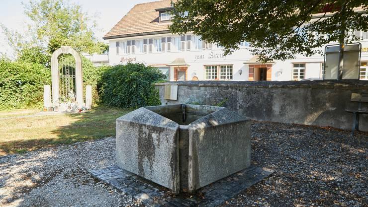 Der schlichte, fast quadratische Brunnen aus den 1970er-Jahren vor der Friedhofskapelle ist unauffällig, ganz im Gegensatz zur früheren Wallfahrtskapelle mit ihrem hohen Treppengiebel, die in der Zeit um 1530 erstellt wurde.