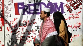 13. Februar 2011: Zwei Tage nach dem Rücktritt von Diktator Hosni Mubarak schreiten zwei Ägypter in Kairo an revolutionären Graffiti in der Hauptstadt Kairo vorbei.John Moore/Getty