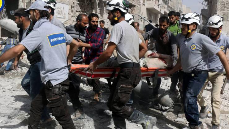 Mitglieder der Hilfsorganisation Weisshelme bringen einen Verletzten in Aleppo in Sicherheit. (Archiv)