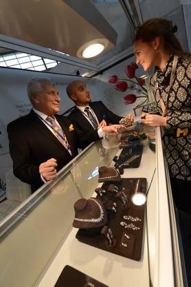 Abgeschlossen in Glasvitrinen funkeln die Steine, über sie beugen sich Verkäufer und Besucher, dazwischen verhandelnde Hände verschiedener Hautfarben.