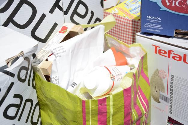Umweltverbrechen: Holzkiste, PVC-Milchtüte und Papier im Plastiksack.