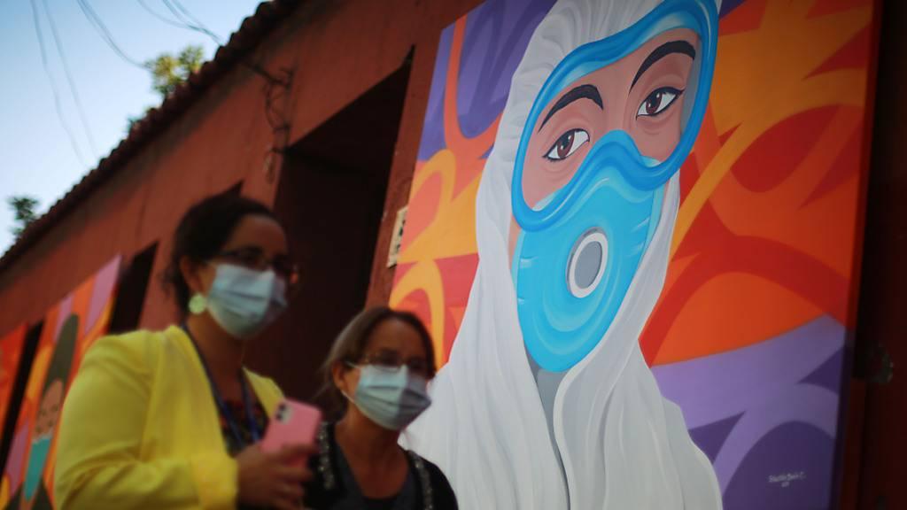 Zwei Frauen mit Masken gehen an einem Wandgemälde zur Anerkennung der Mitarbeiter des Gesundheitswesens bei der Bekämpfung des Covid-19 vorbei. (Archivbild) Foto: Jose Francisco Zuniga/Agencia Uno/dpa