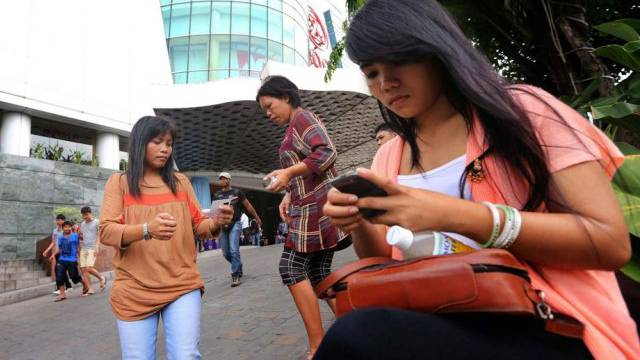 Indonesierinnen informieren sich per Handy über das Beben in Aceh