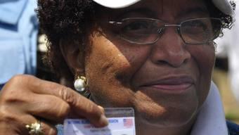 Die Präsidenschaftskandidatin und Friedensnobelpreisträgerin Ellen Johnson-Sirley zeigt ihre Wahlkarte