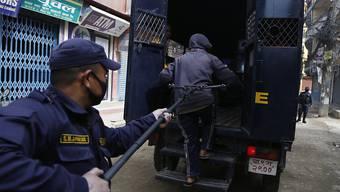 Ein Polizist in Nepal nimmt eine Person fest, die gegen die Ausgangssperre verstossen hat. Wegen der Corona-Pandemie benutzt die Polizei in Nepal lange Klammern.