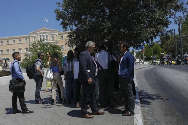Hinter den Menschen ist das Griechische Parlament zu sehen.