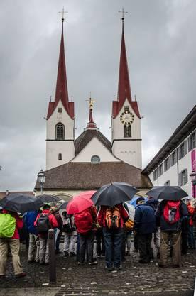 Regenschirm-Meer vor der Klosterkirche Muri auf der verregneten zweiten Etappe