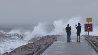 HANDOUT - Zwei Männer fotografieren in Galveston, Texas, Wellen, die an der Küste brechen. Hurrikan «Laura» gewinnt weiter an Stärke. Foto: Jennifer Reynolds/The Galveston County Daily News/AP/dpa - ACHTUNG: Nur zur redaktionellen Verwendung und nur mit vollständiger Nennung des vorstehenden Credits