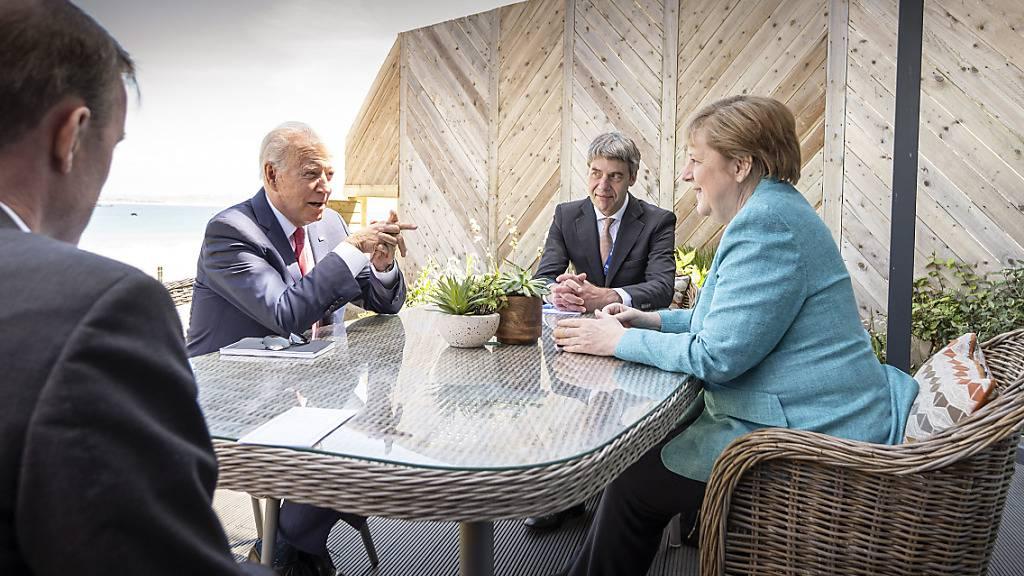 HANDOUT - Bundeskanzlerin Angela Merkel (CDU) und US-Präsident Joe Biden (2.v.l.) sitzen zu Beginn ihres Gesprächs am Rande des G7-Gipfels mit ihren außenpolitischen Beratern Jan Hecker (2.v.r.) und Jake Sullivan (l) zusammen. Foto: Guido Bergmann/Bundesregierung/dpa