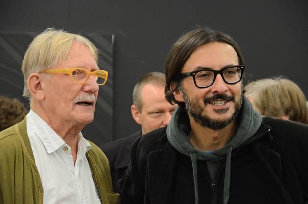 """Die beiden mitwirkenden Künstler Remigius Sep (links) und Paul Takács diskutieren Werke aus der Ausstellung """"Truffes & Trouvailles"""" im Kunstraum Baden."""