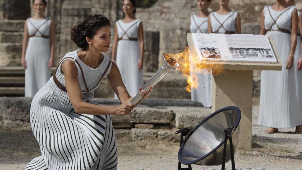 Eine Schauspielerin entfacht das olympische Feuer während der Zeremonie im antiken Olympia in Griechenland