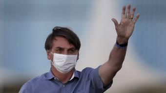 Jair Bolsonaro, Präsident von Brasilien, der mit Covid-19 infiziert ist, trägt eine Schutzmaske, während er an einer Zeremonie vor seinem Amtssitz teilnimmt. Foto: Eraldo Peres/AP/dpa