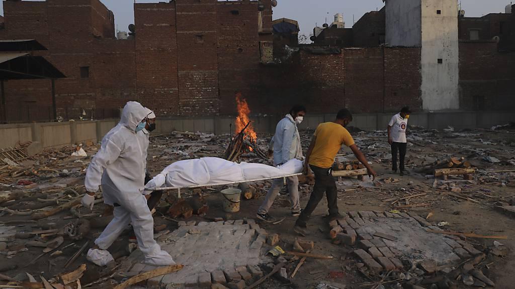 ARCHIV - Familienmitglieder und Freiwillige tragen den Leichnam eines Corona-Opfers zur Einäscherung. Foto: Amit Sharma/AP/dpa