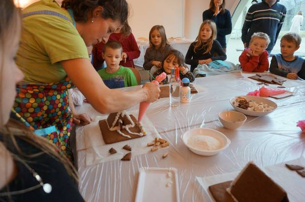 Wer wird wohl in diesem Lebkuchenhaus wohnen fragen sich die Kinder während sie aufmerksam lernen wie man das Haus baut