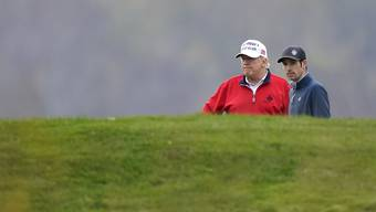 Donald Trump (l), amtierender Präsident der USA, spielt Golf im Trump National Golf Club in Sterling. Foto: Manuel Balce Ceneta/AP/dpa