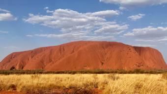"""ARCHIV - Der Uluru, 348 Meter hohen Felsen mitten in der australischen Wüste, der früher unter dem Namen «Ayers Rock» bekannt war. (zu dpa """"Angst vor Corona: Australiens heiliger Berg Uluru wieder geschlossen"""") Foto: Christoph Sator/dpa"""