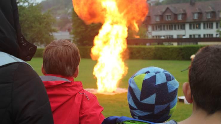 Staunend verfolgen die Schüler das spektakuläre Feuer. Die Feuerwehrmänner haben aber alles unter Kontrolle und löschen den Brand professionell.
