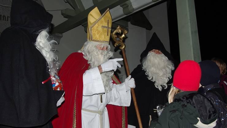 Der Samichlaus und seine Schmutzli beschenken nach ihrer Fährefahrt über den Rhein in Kaiseraugst die wartenden Kinder. hcw