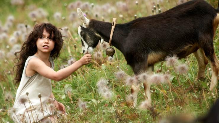 """Heidi (Anuk Steffen) mit einer Geiss auf der Alp, Szene aus dem Film """"Heidi"""" von Alain Gsponer."""