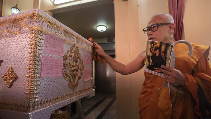Ein buddhistischer Mönch betet am Sarg des verurteilten Serienmörders Si Ouey, bevor er im Wat Bang Phraek Tai-Tempel in Thailand eingeäschert wird. Foto: Sakchai Lalit/AP/dpa