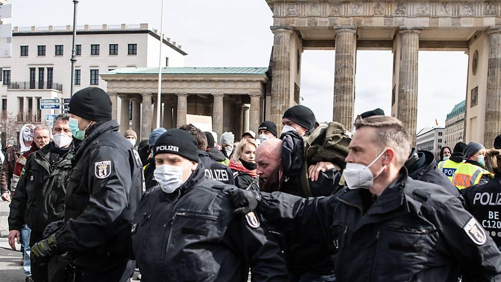 Ein Teilnehmer an einer Demonstration von Rechtsextremisten und sogenannten Reichsbürgern wird von der Polizei am Brandenburger Tor festgenommen. Foto: Paul Zinken/dpa