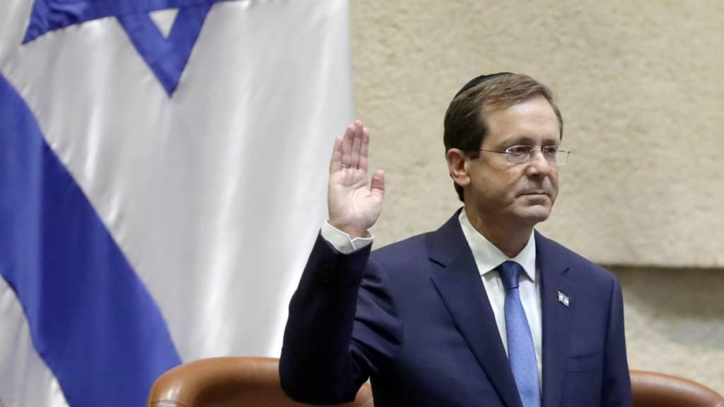 Izchak Herzog, neuer Präsident von Israel, hebt während seiner Vereidigungszeremonie im israelischen Parlament die Hand. Foto: Sebastian Scheiner/AP/dpa Foto: Sebastian Scheiner/AP/dpa