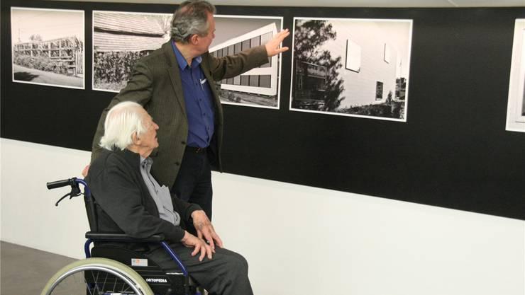 Erwin und Christoph Rehmann betrachten Fotografien von Philipp Fuchs.