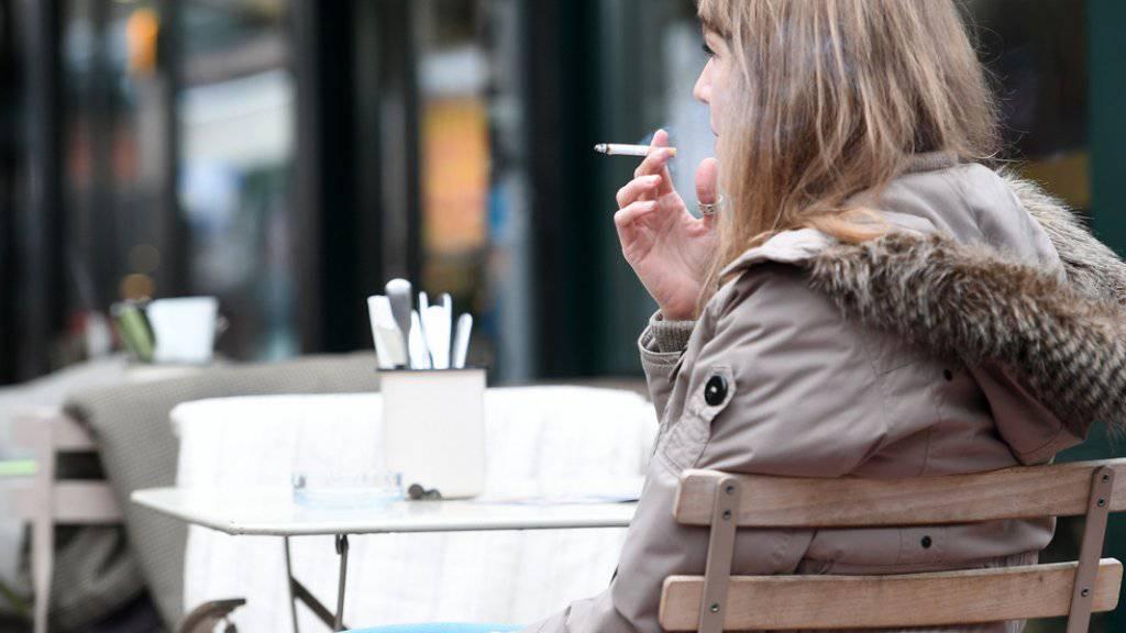 Frau mit Zigarette vor einem Restaurant in Wien.