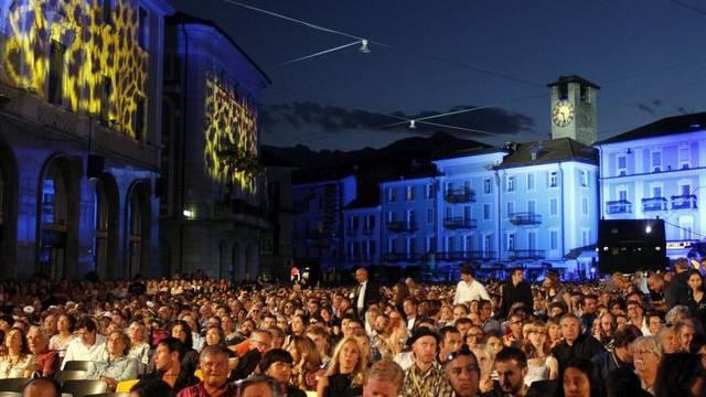 Besucherinnen und Besucher des Filmfestivals auf der beleuchteten Piazza Grande