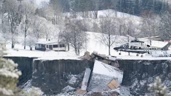 dpatopbilder - Ein Helikopter fliegt über die Stelle, an der ein Erdrutsch zahlreiche Häuser in die Tiefe gerissen oder zerstört hat. Foto: Fredrik Hagen/NTB/dpa