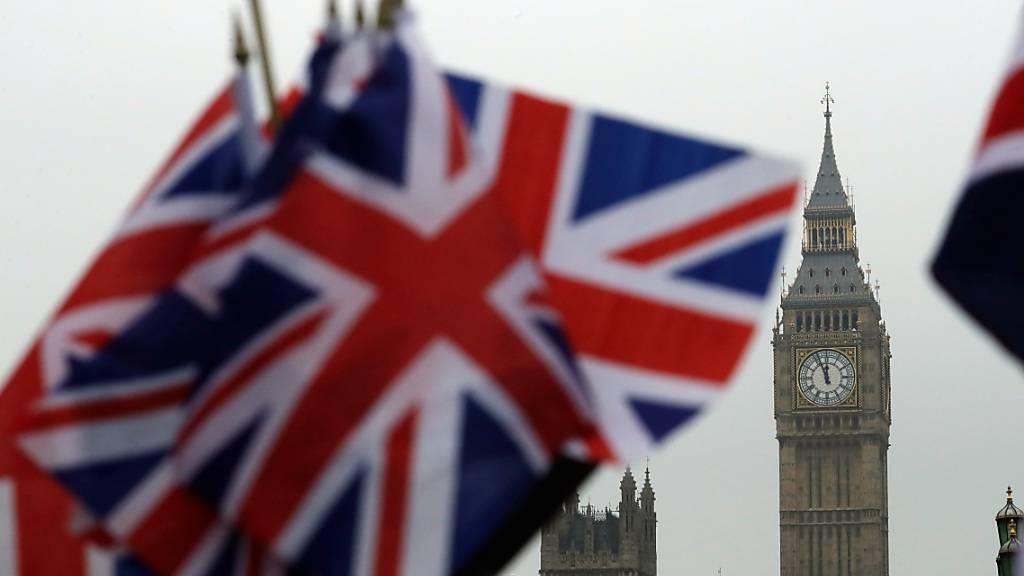 ARCHIV - Britische Flaggen wehen in der Nähe des berühmten Uhrturms Big Ben. Die Unterhändler beraten immer noch über den Brexit-Handelspakt. Foto: Matt Dunham/AP/dpa