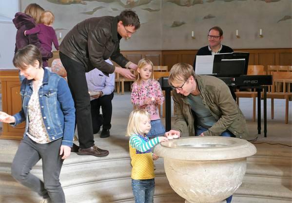 Kinder stellen mit Hilfe ihrer Eltern eine Kerze auf den Taufstein
