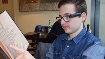 Der blinde Kelvin Meyrat liest mit Hilfe seiner Orcam (am linken Brillenrand) die Speisekarte in der Sinser Pizzeria.