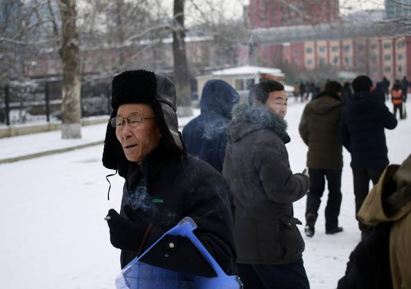 A North Korean man smokes a cigarette as he walks on a snow-covered street in Pyongyang, North Korea, where the winter season has started, on Sunday, Dec. 16, 2018. (AP Photo/Dita Alangkara)