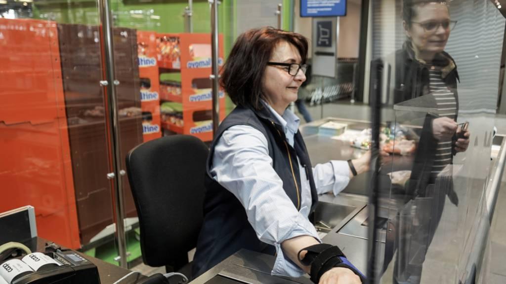 Detailhandel schützt Kunden und Angestellte: Eine Coop-Kassiererin hinter einer Plexiglasscheibe in der Filiale am Bahnhof von Biel.
