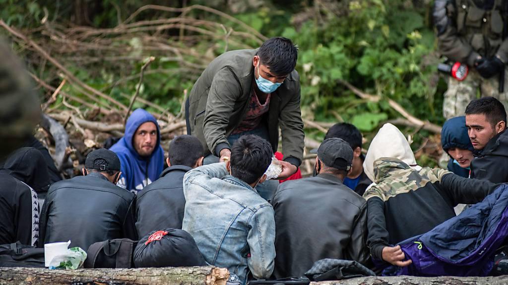 Afghanische Flüchtlinge, die an der polnisch-belarussischen Grenze festsitzen, warten in einem behelfsmäßigen Lager. Die Gruppe aus etwa 30 Menschen sitzt seit Tagen an der Ostgrenze Polens fest. Sie wollen nach Angaben des polnischen Grenzschutzes nicht mehr zurück ins Nachbarland Belarus. Foto: Attila Husejnow/SOPA Images via ZUMA Press Wire/dpa