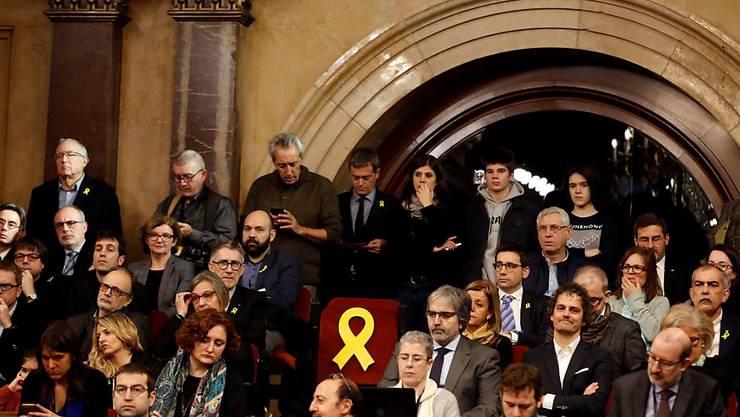 Das neue katalanische Parlament ist erstmals nach dessen Auflösung wieder zusammengetreten. Die Sitze der Separatisten, die in Haft sind und deshalb nicht an der Sitzung teilnehmen können, wurden mit gelben Schleifen dekoriert.