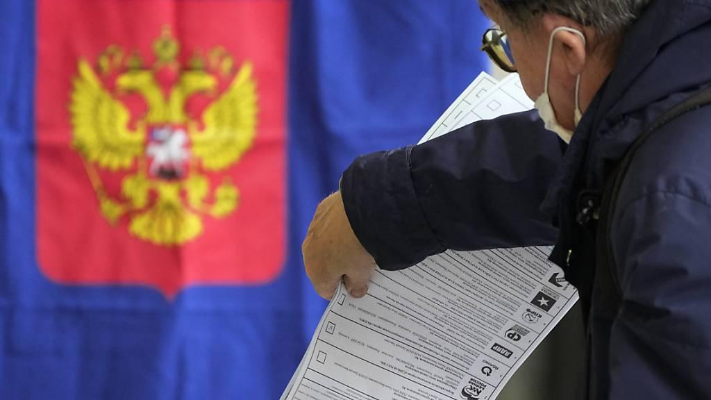Ein Mann gibt während der Wahlen zur Staatsduma, dem Unterhaus des russischen Parlaments, in einem Wahllokal seine Stimme ab. Foto: Dmitri Lovetsky/AP/dpa