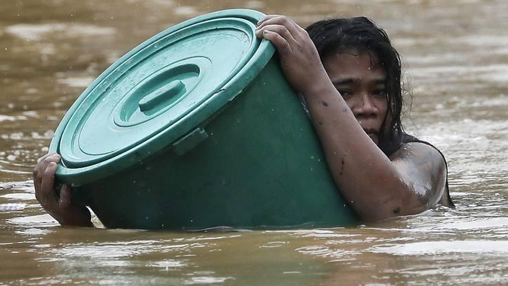 Eine Anwohnerin hält sich an einen Plastikbehälter als Schwimmboje fest, während sie in dem steigenden Hochwasser schwimmt. Foto: Aaron Favila/AP/dpa