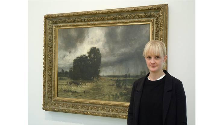 Gastkuratorin Karoliina Elmer vor einem Bild des Malers Adolf Stäbli.