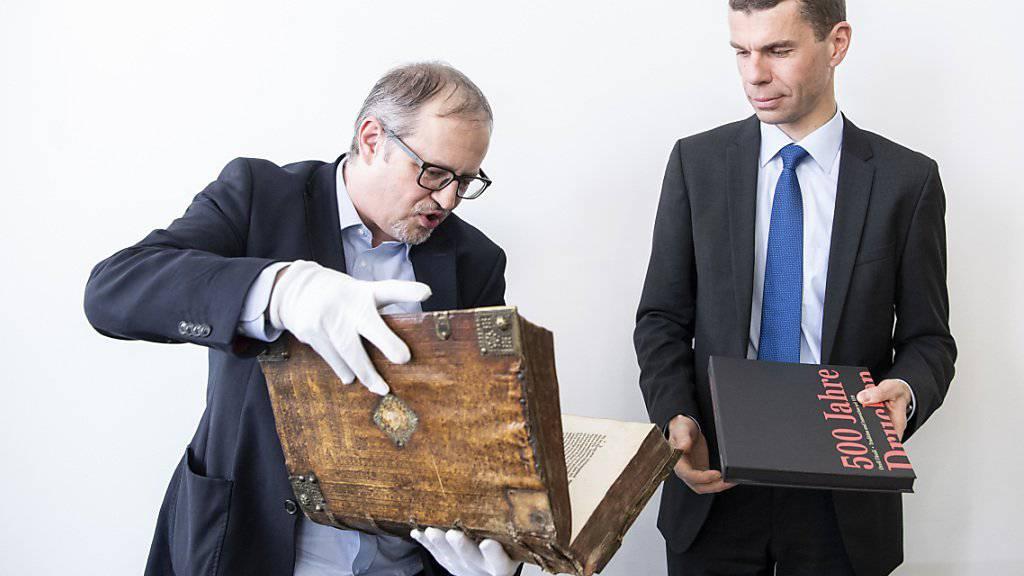 Prunkstücke aus dem Hause Orell Füssli: Historiker und Archivar Adrian Scherrer (links) hält eine Ausgabe der Zwingli-Bibel in seinen Händen, Martin Buyle CEO bei Orell Füssli, die Festschrift zum 500-Jahr-Jubiläum.