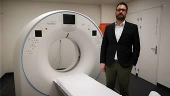 Der neue Stolz des Spitals Menziken: der Computertomograph, neben dem Direktor Daniel Schibler steht.