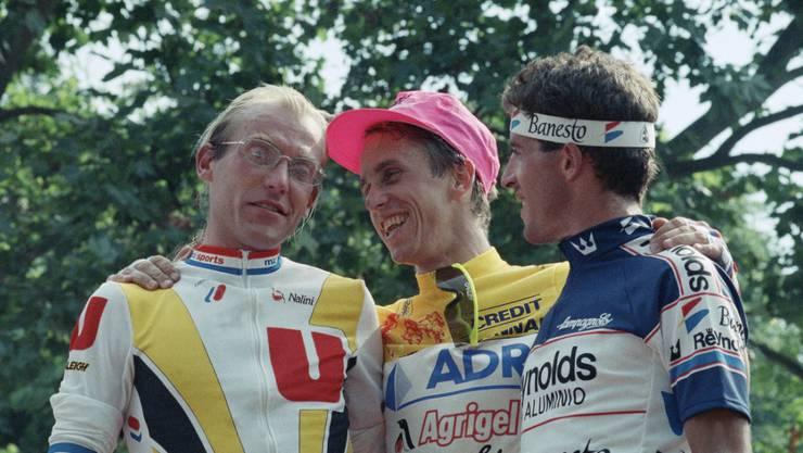Greg LeMond (Mitte) versucht den geschlagenen Laurent Fignon (links) aufzumuntern; Pedro Delgado wurde Gesamtdritter