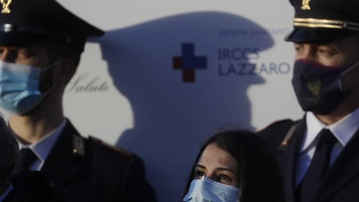 Die italienische Krankenschwester Claudia Alivernini (M) hat als erste Person in Italien den Corona-Impfstoff von Pfizer im Spallanzani Krankenhaus erhalten. Foto: Gregorio Borgia/AP/dpa