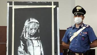 Ein italienischer Polizist bewacht die Türe, welche vermutlich von Banksy bemalt wurde.