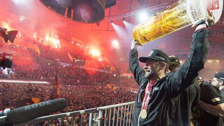 SCB-Captain Martin Plüss präsentiert die Trophäe den Berner Fans in der PostFinance Arena in Bern.