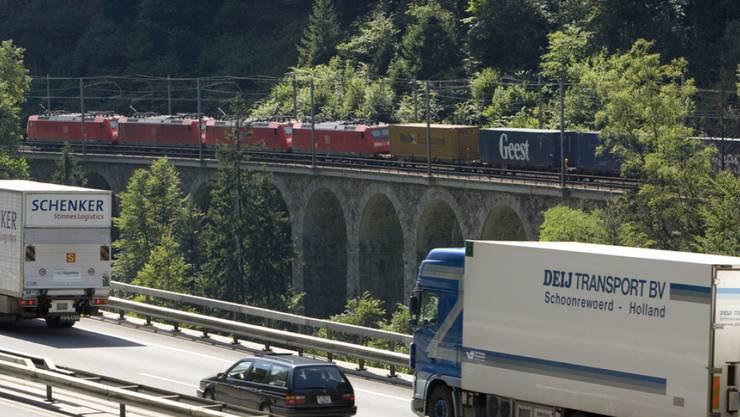 Ein Güterzug ist auf der Gotthardstrecke bei Gurtnellen unterwegs - auf der parallel verlaufenden Autobahn fahren Lastwagen in Richtung Süden (Archivbild).