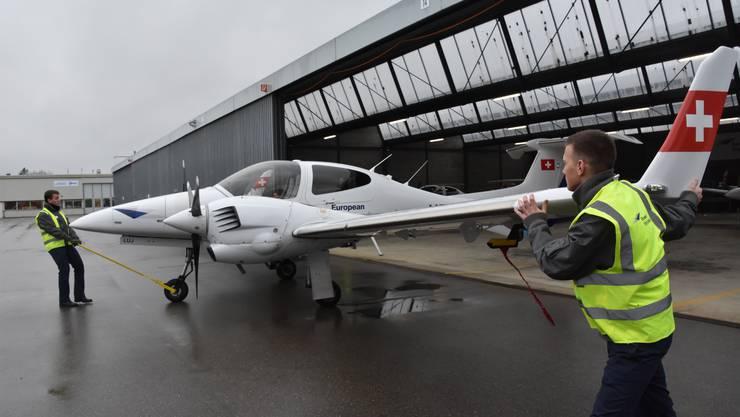 Die zweimotorige DA-42 wird von den Schülern aus dem Hangar gezogen.