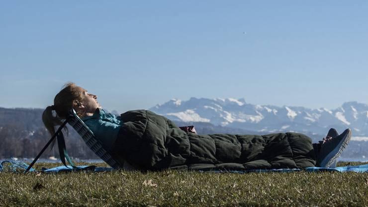 Eine Frau geniesst das frühlingshafte Wetter am Zürichsee, 16. Februar.