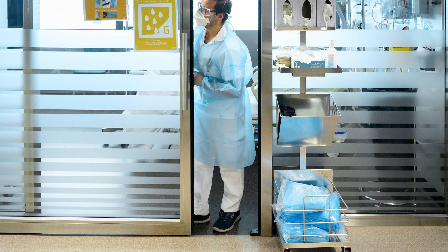 Ein medizinischer Mitarbeiter betreut im Universitätsspital Lausanne einen Covid-19-Patienten. (Symbolbild)